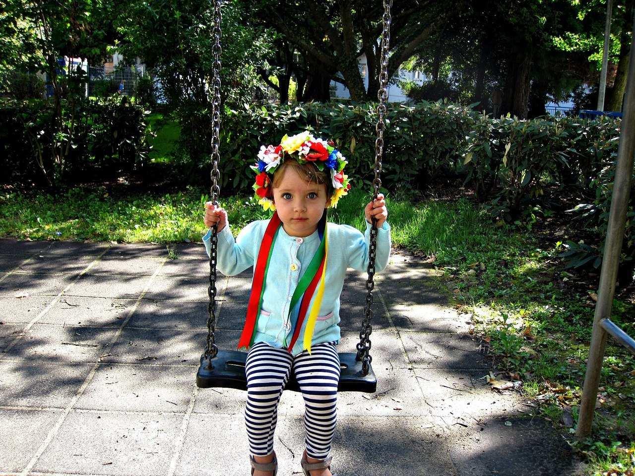 Маленька дівчинка на гойдалці